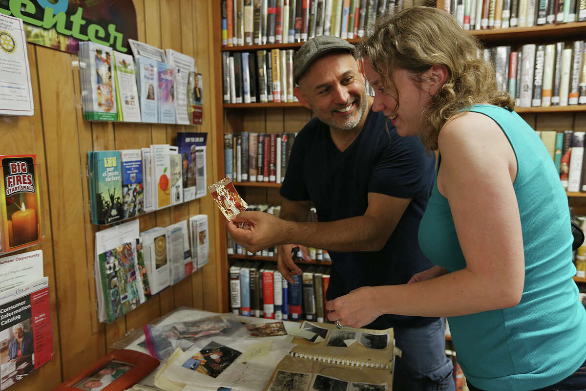 Mark Zavala and his wife, Megan Zavala, of Burbank, California, react after finding family photos at the Wimberley Village Library in Wimberley, Texas on Thursday, May 28, 2015. A historic flood destroyed an estimated 70 homes in the area. His parents house was one of them. The library was the receiving point for photographs lost in the Saturday night flood.