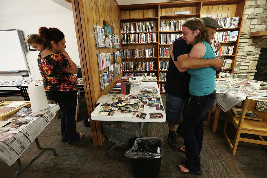 Mark Zavala, 39, and his wife, Megan Zavala, 32, of Burbank, California, hug after finding family photos at the Wimberley Village Library in Wimberley, Texas on Thursday, May 28, 2015. A historic flood destroyed an estimated 70 homes in the area. His parentÕs house was one of them. The library was the receiving point for photographs lost in the Saturday night flood. On the left is ZavalaÕs sister, Kiara Zavala, 33, and her daughter, Selene, 3. Photo: JERRY LARA, San Antonio Express-News / © 2015 San Antonio Express-News