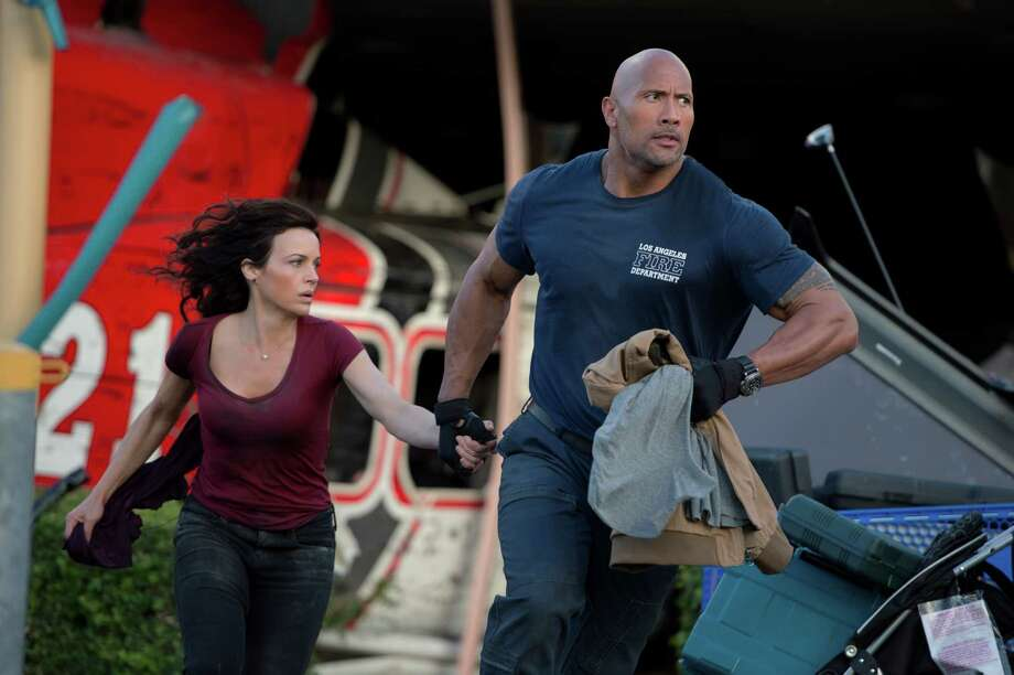 """Carla Gugino as Emma and Dwayne Johnson as her ex-spouse, Ray, flee the destruction in action thriller """"San Andreas."""" Photo: Jasin Boland / Photos By Jasin Boland / © 2014 Warner Bros. Entertainment Inc., WV Films IV LLC and Ratpac-Dune Entertainment LLC—U.S., Canada, Bahamas & Bermuda  © 201"""
