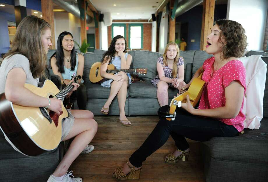 Greenwich singer-songwriter Caroline Jones, right, plays along with contest winners, from left, Greens Farms Academy junior Julia McGonagle, Greenwich High School senior Julia Hava Rosenfeld, Middlesex Middle School eighth-grader Evelyn Sload, and Greenwich High School senior Sophia Lanuza at the Arch Street Teen Center in Greenwich, Conn. Thursday, May 28, 2015.  Jones will perform the free Arch Street Acoustic concert with the four contest winners at the Teen Center on Friday, May 29 at 7:30 p.m..  Grand prize winner Julia McGonagle will also perform on Jones' Sirius XM Coffee House radio show Art & Soul. Photo: Tyler Sizemore / Greenwich Time