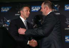 Team general manager Doug Wilson (left) welcomes Peter DeBoer as the new head coach of the San Jose Sharks during a news conference at the SAP Areana in San Jose, Calif. on Thursday, May 28, 2015.