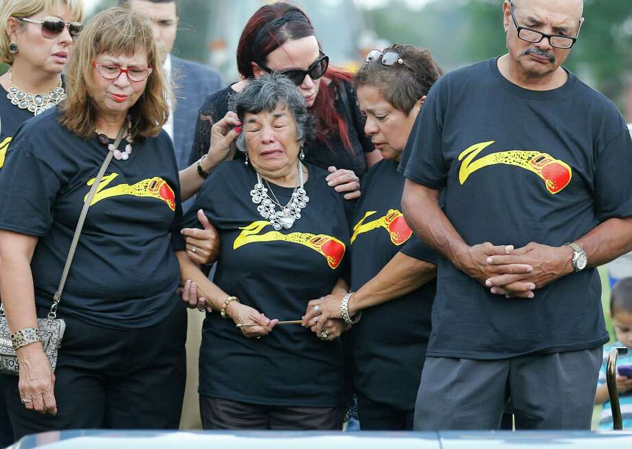 Matriarch Pauline Ayala (center) is comforted by family and friends as the casket of Tony Ayala, Jr. is lowered during the funeral service at San Fernando Cemetery III on Thursday, May 28, 2015. Friends and family of the troubled boxer attended the funeral dressed in black tee shirts emblazoned with the logo of Zarzamora Street Gym where Ayala spent his time training. Earlier in the month, Ayala's body was found in the very same gym and officials determined the cause of death was due to a drug overdose. Photo: Kin Man Hui /San Antonio Express-News / ©2015 San Antonio Express-News