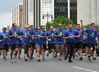 Law Enforcement officers carry the Special Olympics Torch  down Washington Ave. toward City Hall on Thursday, May 28, 2015 in Albany, N.Y.  (Lori Van Buren / Times Union)