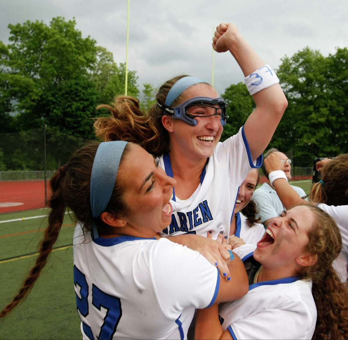 Darien's Mariah Matheis, center, is hoisted by her teammates, Gabriella Noto, left, and Isabella Scribiano after scoring the winning goal in the FCIAC Girls Lacrosse Championship at Brien McMahon High School in Norwalk, Conn. on Thursday, May 28, 2015. Darien defeated New Canaan 13-12 in triple overtime.