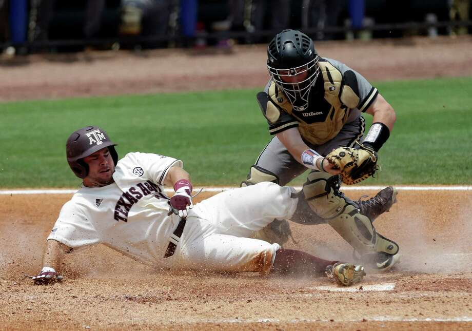 Texas A&M's Mitchell Nau (30) is tagged out by Vanderbilt's Jason Delay (5) as he slides into home plate  during the third inning of a game at the Southeastern Conference college baseball tournament at the Hoover Met, Saturday, May 23, 2015, in Hoover, Ala. (AP Photo/Butch Dill) Photo: Butch Dill, FRE / Associated Press / FR111446 AP