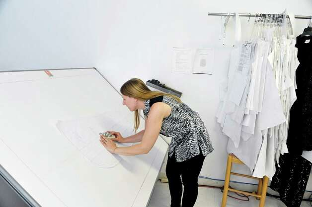 Tara Wheeler, assistant designer to Ursula, uses a mouse on a paper pattern for a jacket inside the Ursula of Switzerland building on Tuesday, May 26, 2015, in Waterford, N.Y.  The mouse is used to capture points on the paper pattern and digitizes the pattern so it can be worked in a computer program.  The dress manufacturer is housed in an old ribbon factory.      (Paul Buckowski / Times Union) Photo: PAUL BUCKOWSKI / 00031965A