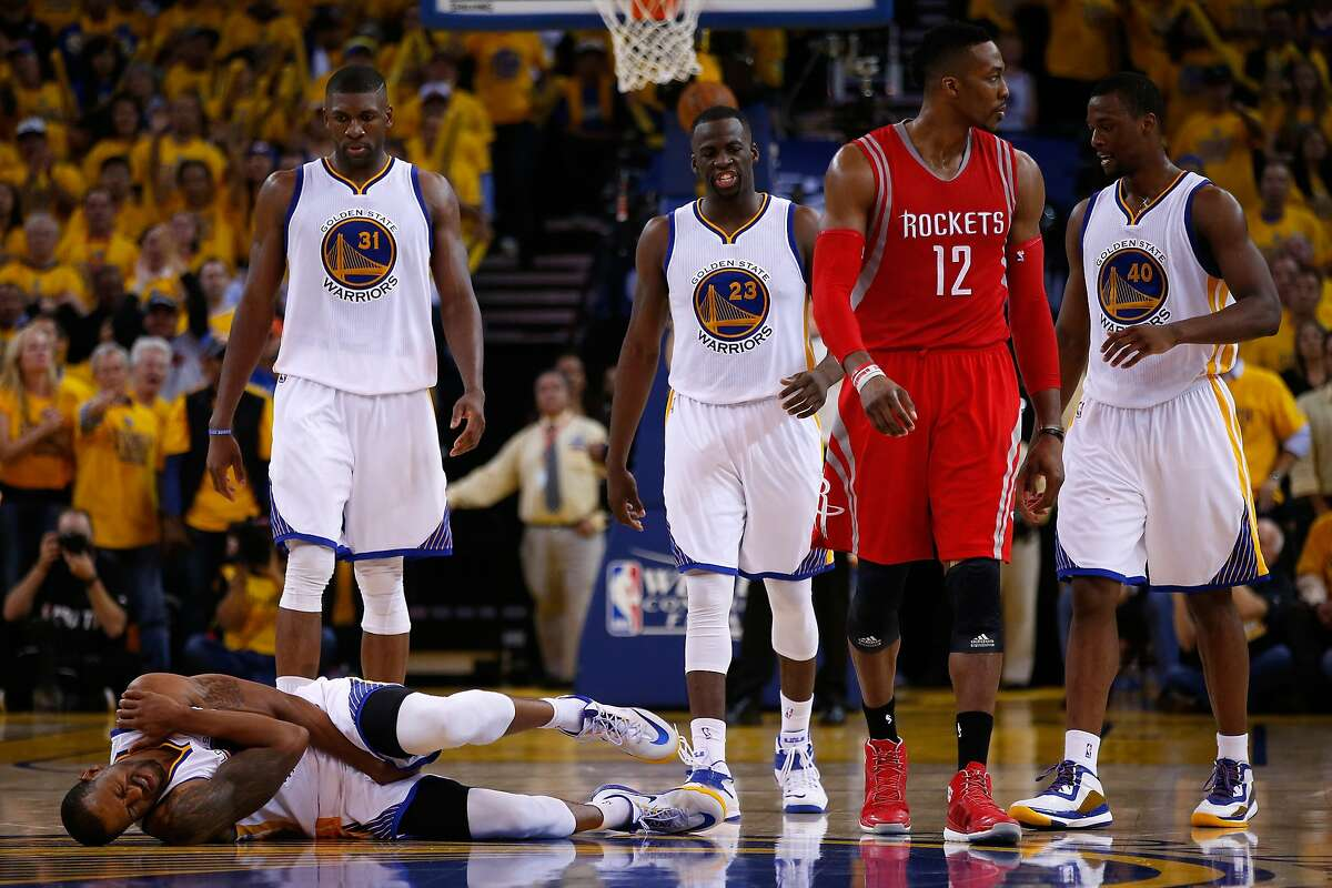 OAKLAND, CA - MAY 27: Andre Iguodala #9 of the Golden State Warriors holds his shoulder as Dwight Howard #12 of the Houston Rockets walks away in the second half during game five of the Western Conference Finals of the 2015 NBA Playoffs at ORACLE Arena on May 27, 2015 in Oakland, California. NOTE TO USER: User expressly acknowledges and agrees that, by downloading and or using this photograph, user is consenting to the terms and conditions of Getty Images License Agreement. (Photo by Ezra Shaw/Getty Images)