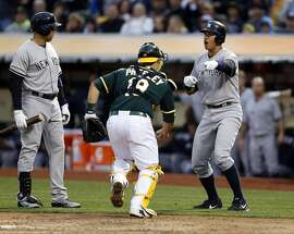 New York Yankees' Alex Rodriguez reacts to an umpire's call that he didn't touch home plate as Oakland Athletics' catcher Josh Phegley goes over to apply tag in 4th inning during MLB game at O.co Coliseum in Oakland, Calif., on Thursday, May 28, 2015. The call was overturned and Rodriguez was called safe.