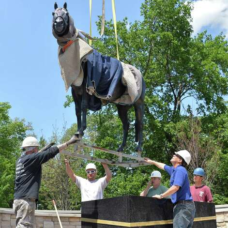 """Tony Bonacio, second from right, directs workers as they place a statue of Storm Cat - trucked from a farm in Kentucky - at """"Centennial Park"""" at the end of Union Avenue Thursday May 28, 2015 in Saratoga Springs, NY.  The statue will remain until Aug 1, when a Native Dancer and rider statue will take its place in the permanent park.  (John Carl D'Annibale / Times Union) Photo: John Carl D'Annibale / 00032036A"""