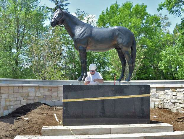 Bonacio Construction site supervisor Jack Hopkins finishes up installation of a statue of Storm Cat at OCentennial ParkO at the end of Union Avenue Thursday May 28, 2015 in Saratoga Springs, NY.  The statue will remain until Aug 1, when a Native Dancer and rider statue will take its place in the permanent park.  (John Carl D'Annibale / Times Union) Photo: John Carl D'Annibale / 00032036A