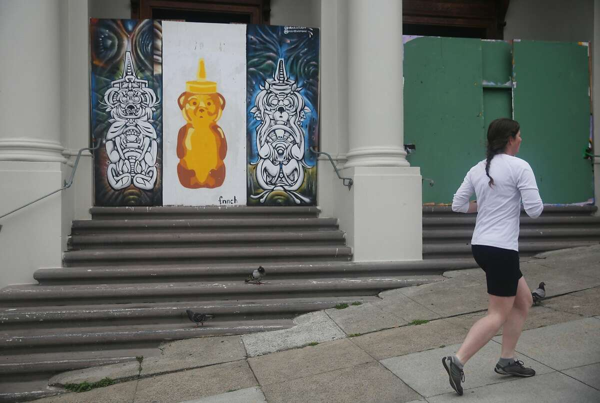 A jogger runs past a large honey bear by street artist Fnnch at Dolores and Cumberland Streets on Wednesday, May 27, 2015 in San Francisco, Calif.