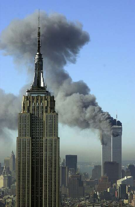 In this Tuesday, Sept. 11, 2001 file photo, plumes of smoke rise from the World Trade Center buildings in New York. The Empire State building is seen in the foreground. Photo: Patrick Sison, Associated Press