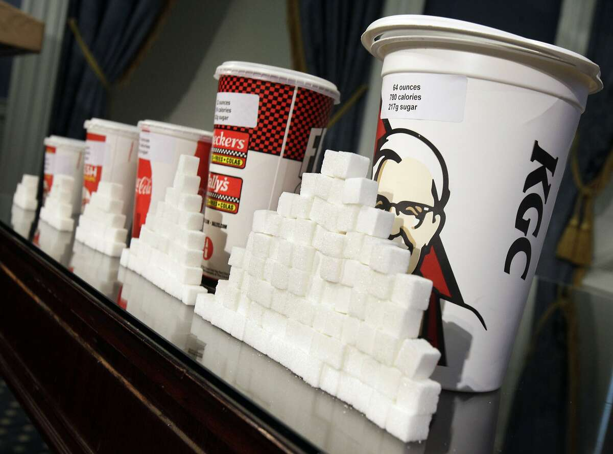 This Thursday, May 31, 2012 file photo shows a display of various size soft drink cups next to stacks of sugar cubes at a news conference at New York's City Hall. New research greatly strengthens the case against soda and other sugary drinks as culprits in the obesity epidemic. Two major experiments found that children and teens gained less weight when they regularly drank calorie-free beverages instead of sugary ones. A third study gives the first clear evidence that consuming sugary drinks interacts with genes that affect weight. Scientists say the results add weight to the push for taxes, size limits and other policies to curb consumption. (AP Photo/Richard Drew, File)