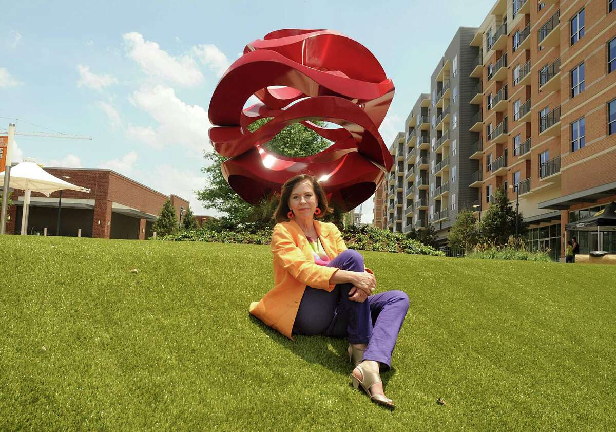 """Mexican sculptor Yvonne Domenge, of Mexico City, in front of her red sculpture """"Wind Wave"""" that was recently installed in the Hughes Landing waterfront.Photograph by David Hopper."""