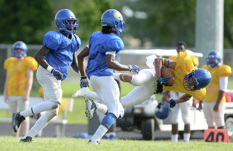 An offensive player is tripped up by the defense after completing a downfield pass during the Ozen Panthers' annual spring football scrimmage Thursday.  Photo taken Thursday, May 28, 2015  Kim Brent/The Enterprise Photo: Kim Brent / Beaumont Enterprise