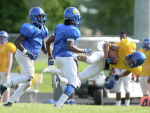 An offensive player is tripped up by the defense after completing a downfield pass during the Ozen Panthers' annual spring football scrimmage Thursday.  Photo taken Thursday, May 28, 2015  Kim Brent/The Enterprise
