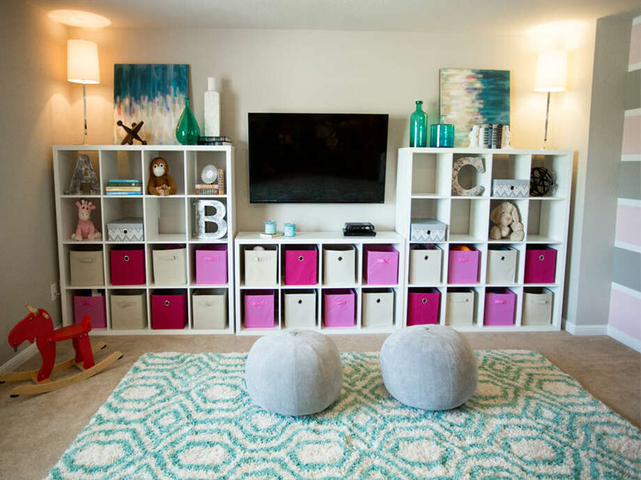 A wall of a play room designed for two girls, ages 1 and 5, features cubbies that hold toys and keep things tidy. Photo: Courtesy Liz Light Interiors