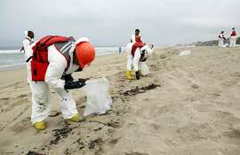 A crew cleans up a beach after balls of tar washed ashore in Manhattan Beach, Calif. on Thursday, May 28, 2015. Popular beaches along nearly 7 miles of Los Angeles-area coastline are off-limits to surfing and swimming after balls of tar washed ashore. The beaches along south Santa Monica Bay appeared virtually free of oil Thursday morning after an overnight cleanup, but officials aren't sure if more tar will show up.