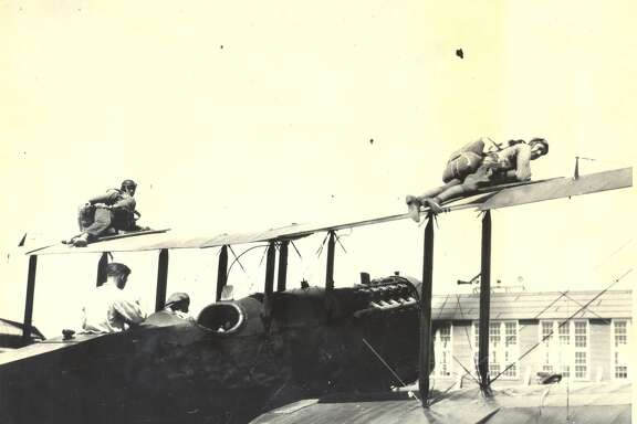 Two paratroopers are shown strapped to the top of the wings of their plane at Brooks Field in this 1924 photo.