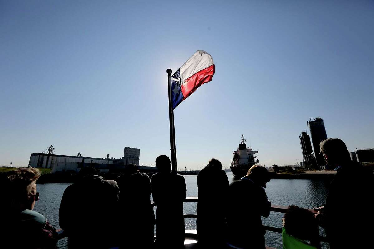 Passengers stand on the bow of the ship as the Texas flag is silhouetted as the Sam Houston travels the Houston Ship Channel on October 24, 2014 in Houston, TX. The Sam Houston offers a free 90 minute round trip cruise along the Houston Ship Channel. Embarking from the port's Sam Houston Pavilion, visiting sightseers aboard the M/V Sam Houston can enjoy passing views of international cargo vessels, and operations at the port's Turning Basin Terminal. The 95-ft. vessel holds up to 90 passengers and features air-conditioned lounge seating as well as standing room outside on the boat's deck.