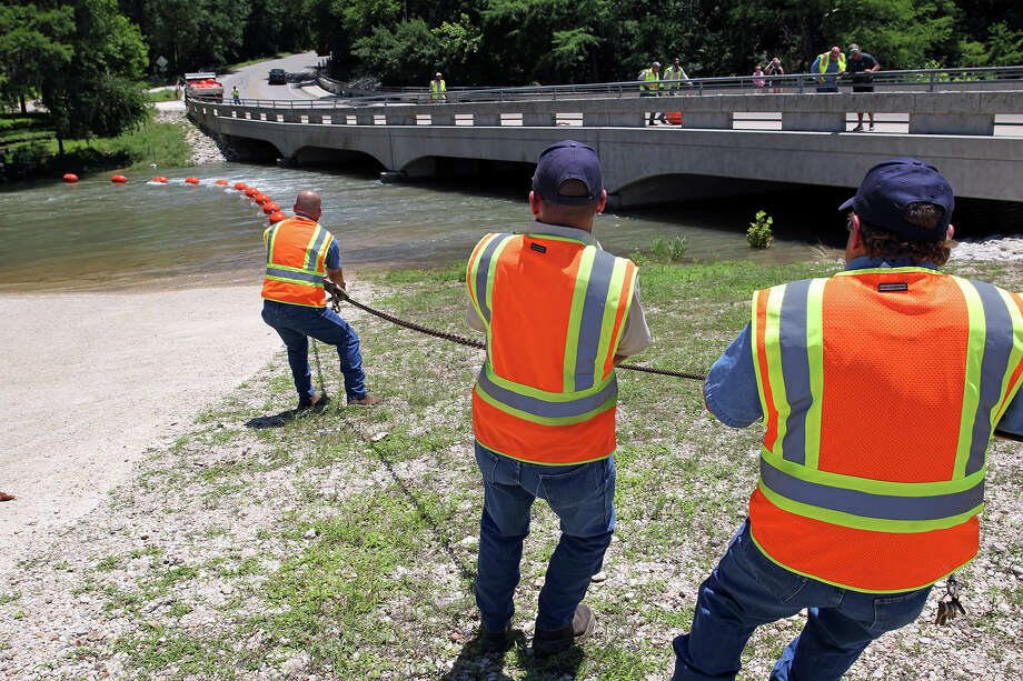 New Braunfels crews stretch a buoy line near the Gruene bridge in anticipation of increased water flow on the Guadalupe River for the weekend in the event the locks are opened at Canyon Dam to release stored flood water.  May 29, 2015. Photo: Tom Reel, San Antonio Express-News