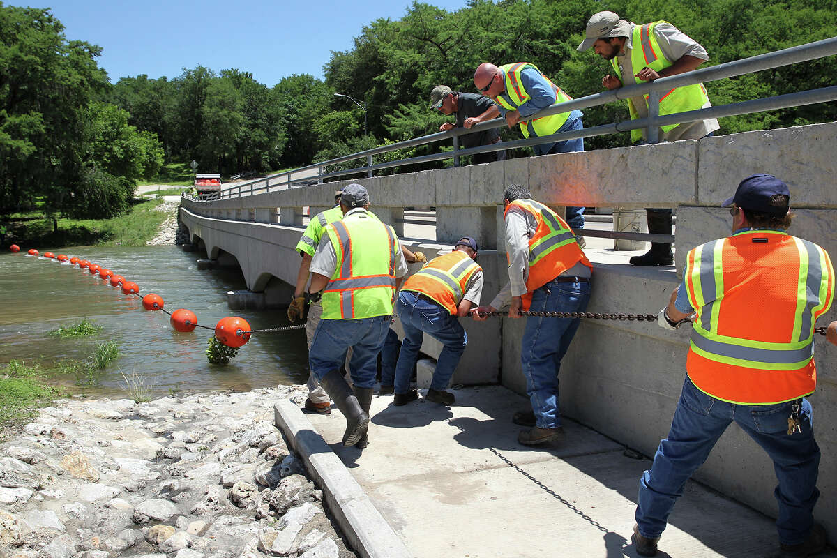 New Braunfels crews stretch a buoy line near the Gruene bridge in anticipation of increased water flow on the Guadalupe River for the weekend in the event the locks are opened at Canyon Dam to release stored flood water. May 29, 2015.