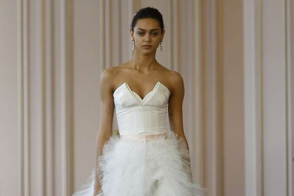 "The Oscar de la Renta Bridal 2016 collection, the first by new designer Peter Copping, featured several gowns with detachable skirts, for versatility, and others with modern bubble hems. This gown, called the ""Zhenya,""  is a white silk faille column gown, with a point d'esprit ruffle overskirt. It retails for $9,990."