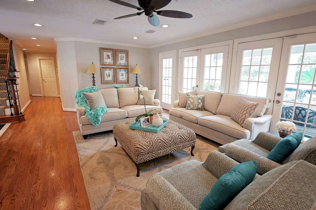 Two neutral sofas from Bassett Furniture give the Minyards ample seating in the living room.Two of the couple's old chairs were reupholstered with a Greek key-patterned fabric.