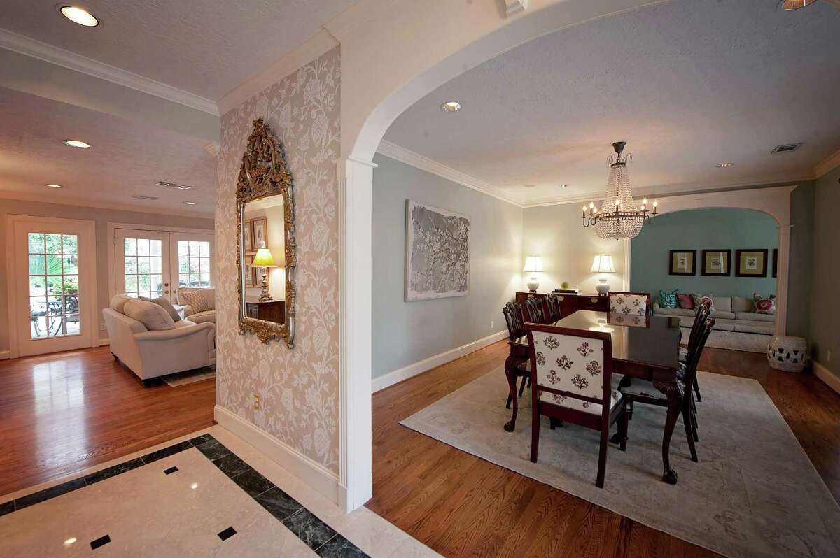 The Minyards lightened up their entryway with a more neutral wallpaper. Its traditional floral print blends with some of the home's warmer tones, including the wood floors.