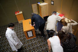 Participants in Room Escape Adventures search for clues to get out of a locked room and escape a zombie. This pictures show a private event at a location outside of San Francisco.