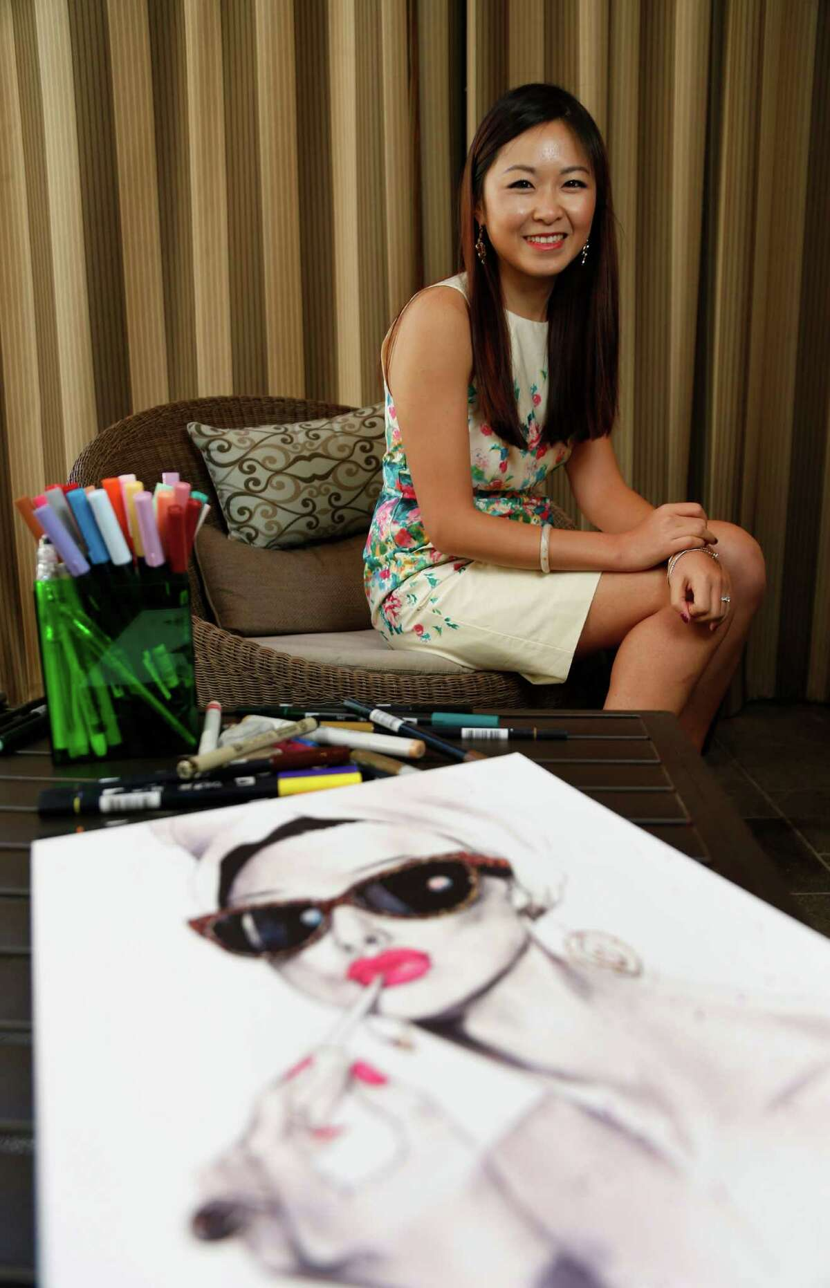 """Style profile on Houston fashion illustrator Rongrong Devoe, with one of her drawings in the foreground, photographed at the Millennium High Building on Wednesday, April 29, 2015, in Houston. Devoe is originally from Qingdao, China, and worked as a concept artist in Shanghai. She moved to NY to pursue a master's in illustration at the Fashion Institute of Technology. She now lives in Houston and illustrated a teen fashion book for Klutz Publishing, due out this summer, and does illustrations for Lé¢Ã©""""é´oreal. ( Karen Warren / Houston Chronicle )"""