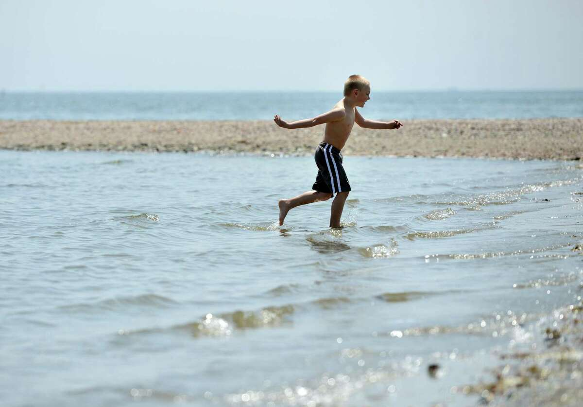 Five-year-old John Esser, of Beacon Falls, runs for the shore after testing the water Friday, May 8, 2015, at Silver Sands State Park in Milford, Conn. According to a study published this month in the Journal of the American Academy of Dermatology, the majority of Americans don't use sunscreen.