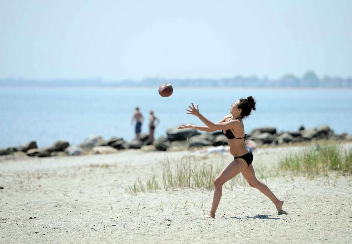 JeAnna Salvatore, of Waterbury, tosses around a football with friends Friday, May 8, 2015, at Silver Sands State Park in Milford, Conn. According to a study published this month in the Journal of the American Academy of Dermatology, the majority of Americans don't use sunscreen.