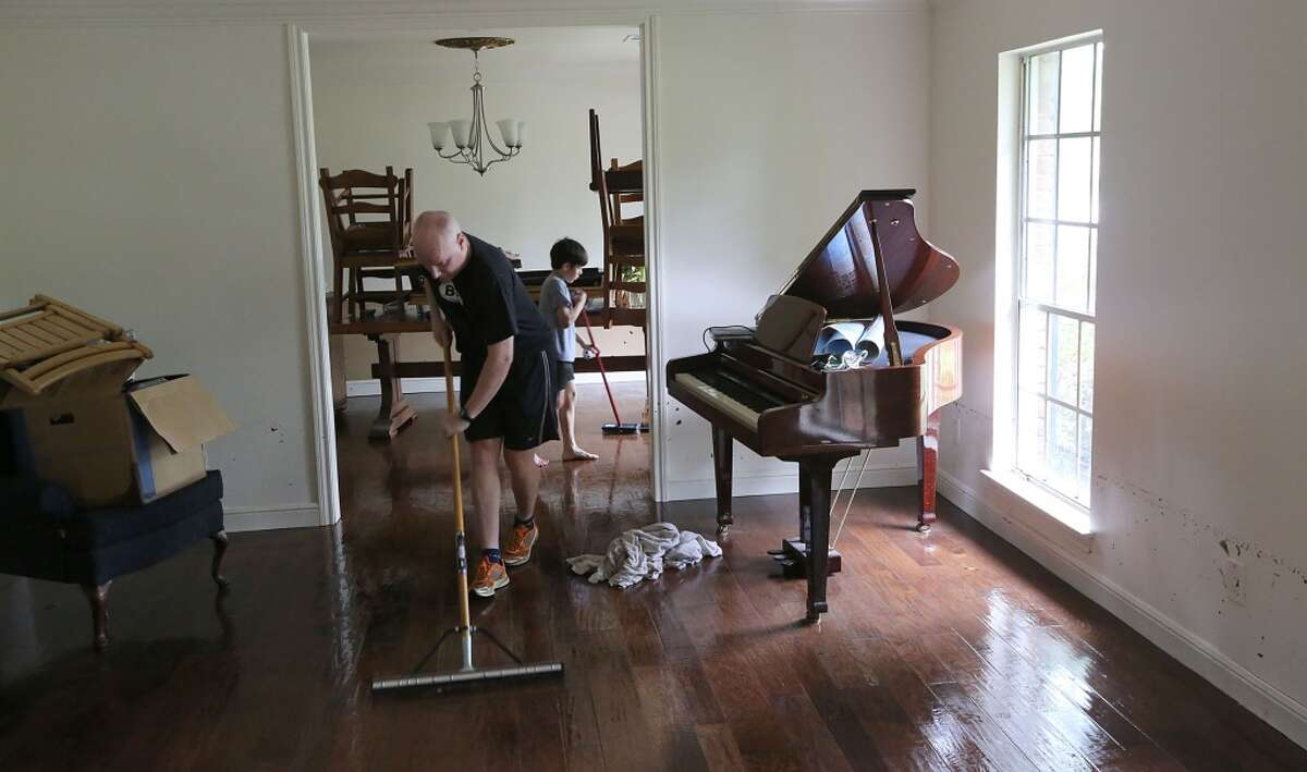 Alex Weisbach mops water while Gabriel Varon sweeps water from the hardwood floors at 5307 S. Braeswood on Tuesday, May 26, 2015 in Houston, TX . The storm brought in two feet of water in their house and knocked down a tree in the front yard.On the right you can see the water mark on the wall. (Photo: Thomas B. Shea/For the Chronicle)