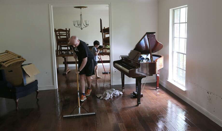 Alex Weisbach mops water while Gabriel Varon sweeps water from the hardwood floors at 5307 S. Braeswood on May 26, 2015 in Houston. The storm brought two feet of water into their home and knocked down a tree in the front yard. Photo: For The Chronicle