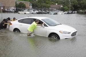 Joseph Chipello, right, and others push a car to dry roadway after the elderly man driving stalled in flood water along North Braeswood near Hillcroft Tuesday, May 26, 2015, in Houston. ( Melissa Phillip / Houston Chronicle )