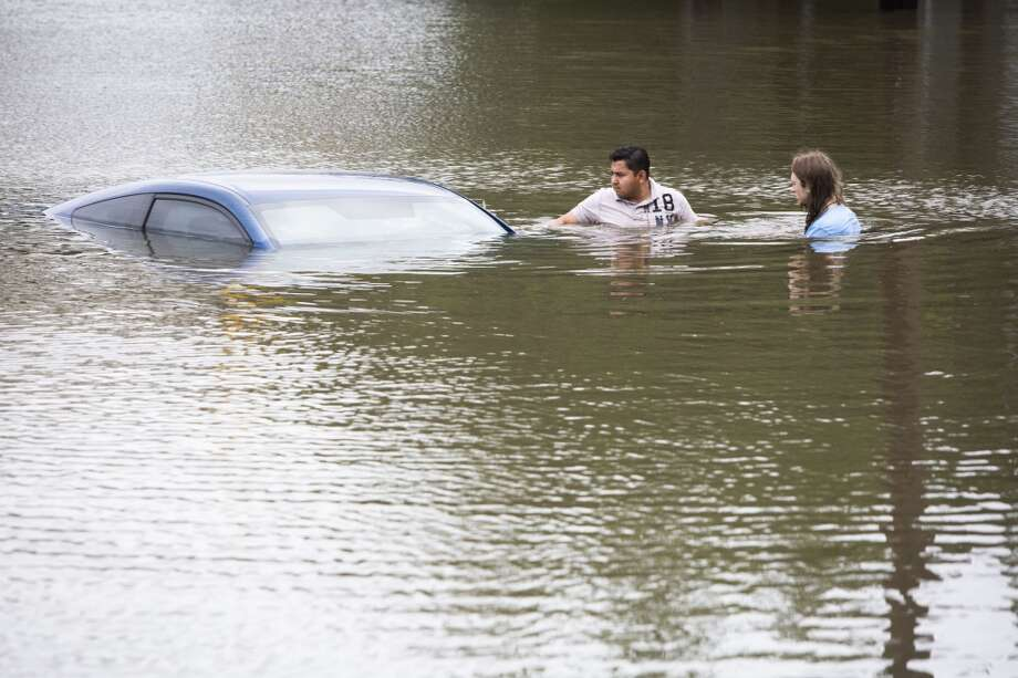 Roberto Salas, left, and Lewis Sternhagen check a flooded car near Willow Waterhole. Photo: New York Times