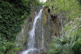Spectators look over the waterfall at the Japanese Tea Garden in Brackenridge Park.