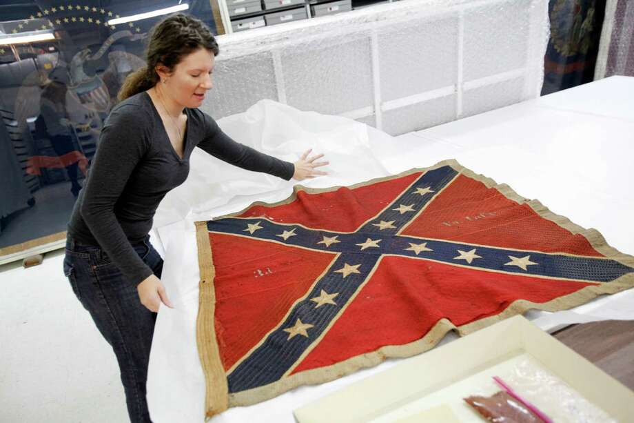 Cathy Wright, curator at the Museum of the Confederacy in Richmond, Va., unfurls a battle flag belonging to the 3rd Virginia Infantry.  A reader says he has no issues  with commemorating the Civil War or the flag that represented Southern states. Photo: Dean Hoffmeyer /AP / Richmond Times-Dispatch
