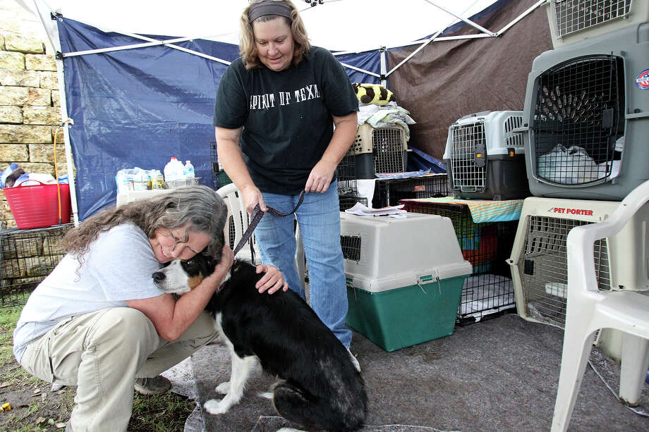 Amanda Woodell hugs a dog brought in to the Wimberley Adooption  Group and Rescue as clean up continues in Wimberly after devastating flooding of the Blanco River with Texas National Guard troops still assisting with search and rescue on May 27, 2015.  Assisting is volunteer Debbie Randall (right). Photo: Tom Reel / San Antonio Express-News