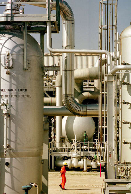 """An oil worker walks through a refinery at Mina Al Ahmadi, south of Kuwait City. OPEC, which is meeting Friday, will """"stick with"""" its present strategy, Abdulmajeed Al-Shatti, a member of Kuwait's Supreme Petroleum Council, said  this month. Photo: Associated Press File Photo / AP"""