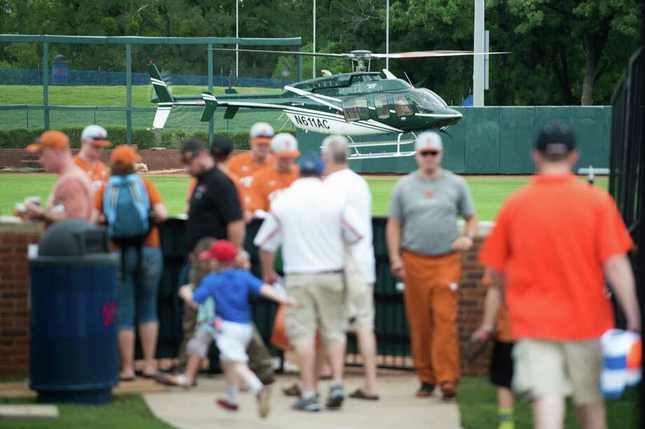 Fans look on as a helicopter dries the outfield during a rain delay before Oregon State and Texas play a game at the Dallas regional of the NCAA college baseball tournament in Dallas, Friday, May 29, 2015. (AP Photo/Cooper Neill) Photo: Cooper Neill, FRE / Associated Press / FR171332 AP