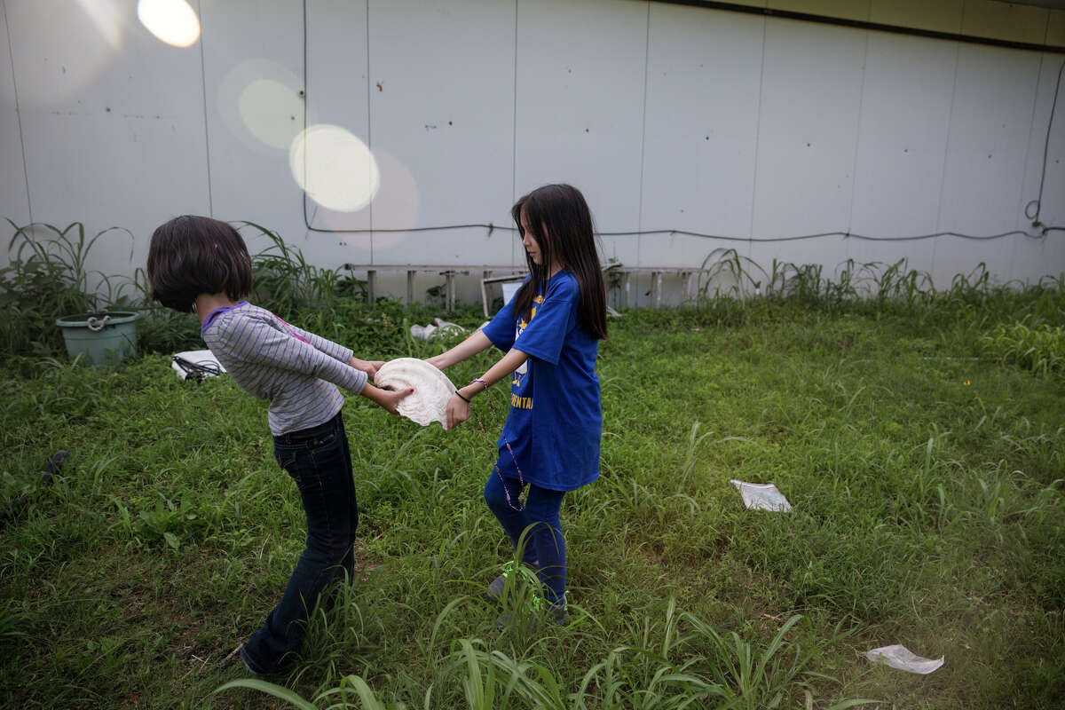 Serenity Bamberger, 7, and Cielo Bamberger, 9, play with their grandmother's shell in the yard of their home in Blanco, Texas on May 29, 2015.