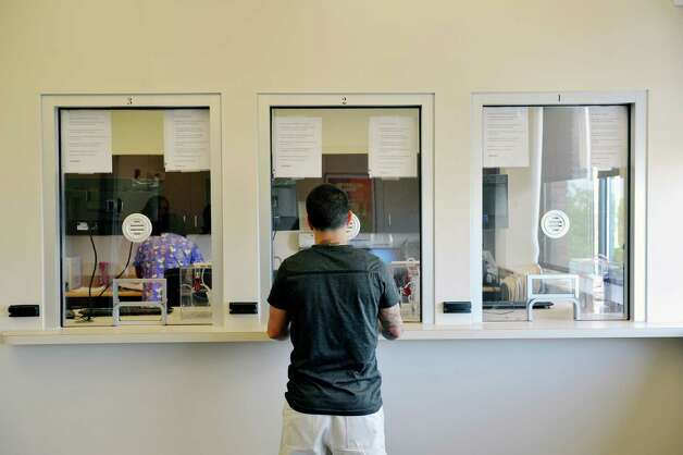 Alexis Santiago-Afanador a client of Capital District Camino Nuevo outpatient and outpatient methadone program stands at the window where clients get their methadone on Wednesday, May 13, 2015, in Albany, N.Y.    (Paul Buckowski / Times Union) Photo: PAUL BUCKOWSKI / 00031767A