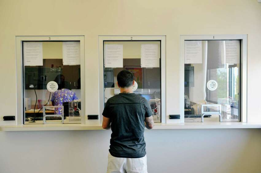 Alexis Santiago-Afanador a client of Capital District Camino Nuevo outpatient and outpatient methadone program stands at the window where clients get their methadone on Wednesday, May 13, 2015, in Albany, N.Y. (Paul Buckowski / Times Union)