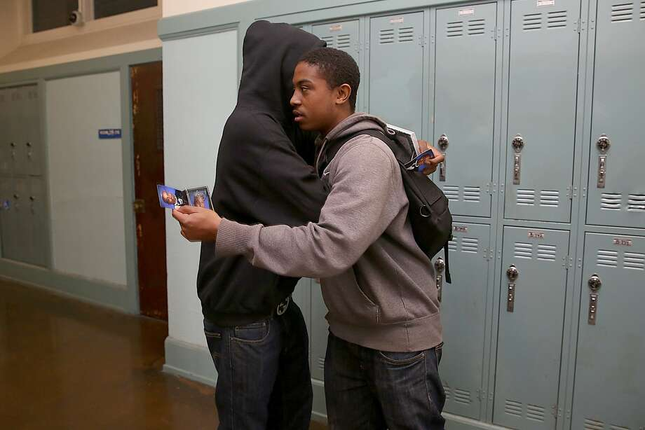 Senior students Jamel Williams (left) and Jamier Scott (right) hug at Balboa High School in San Francisco, California, on Friday, May 22, 2015. Photo: Liz Hafalia, The Chronicle