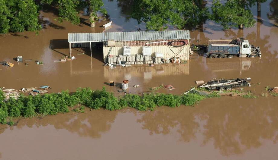A building and dump truck are surrounded by floodwaters from the Brazos River on Saturday, May 30, 2015, near Rosenberg. The Colorado River, in Wharton, and the Brazos and San Jacinto rivers near Houston are the main focus of concern as floodwaters moved from the north and central Texas downstream toward the Gulf of Mexico. Photo: Brett Coomer, Houston Chronicle / © 2015 Houston Chronicle