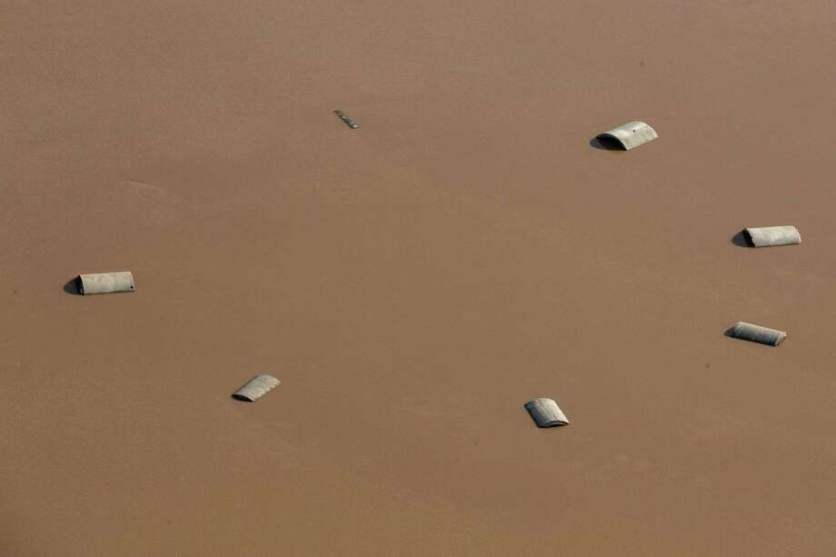 Only the tops of a circle of buildings are seen above floodwaters from the Brazos River on Saturday, May 30, 2015, near Rosenberg. The Colorado River, in Wharton, and the Brazos and San Jacinto rivers near Houston are the main focus of concern as floodwaters moved from the north and central Texas downstream toward the Gulf of Mexico. Photo: Brett Coomer, Houston Chronicle / © 2015 Houston Chronicle