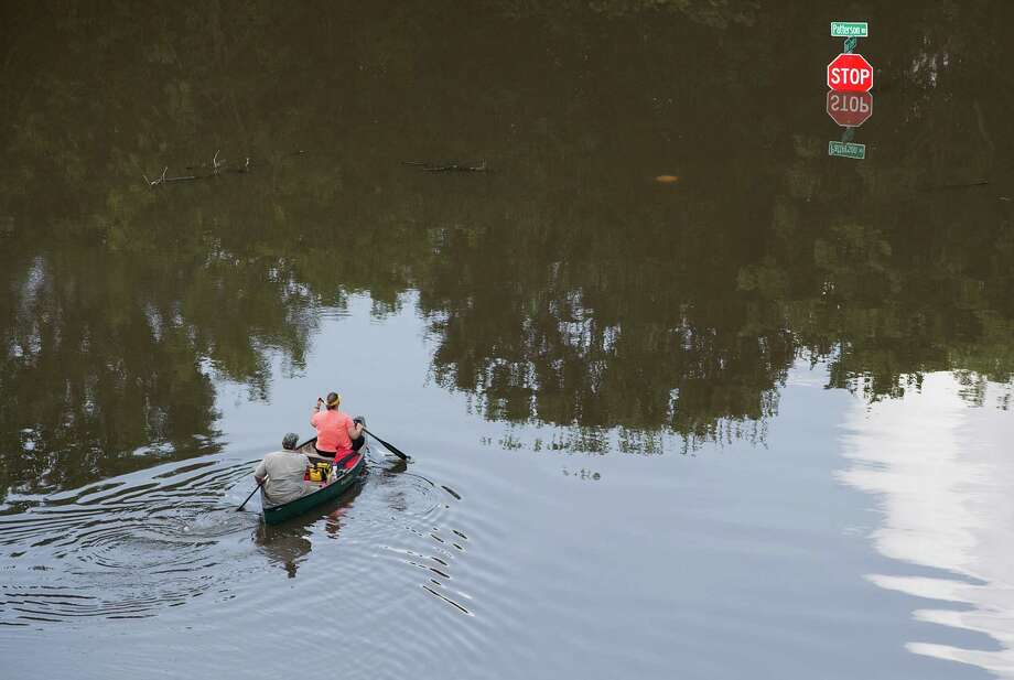 People canoe in floodwaters near Bear Creek Park on Saturday, May 30, 2015, in Houston. The Colorado River, in Wharton, and the Brazos and San Jacinto rivers near Houston are the main focus of concern as floodwaters moved from the north and central Texas downstream toward the Gulf of Mexico. Photo: Brett Coomer, Houston Chronicle / © 2015 Houston Chronicle