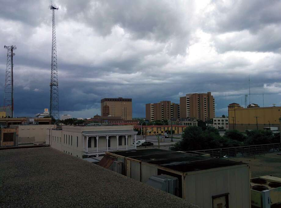 Skies darken over downtown San Antonio as a strong line of showers begin to move through Bexar County. Photo: Chris Quinn, San Antonio Express-News